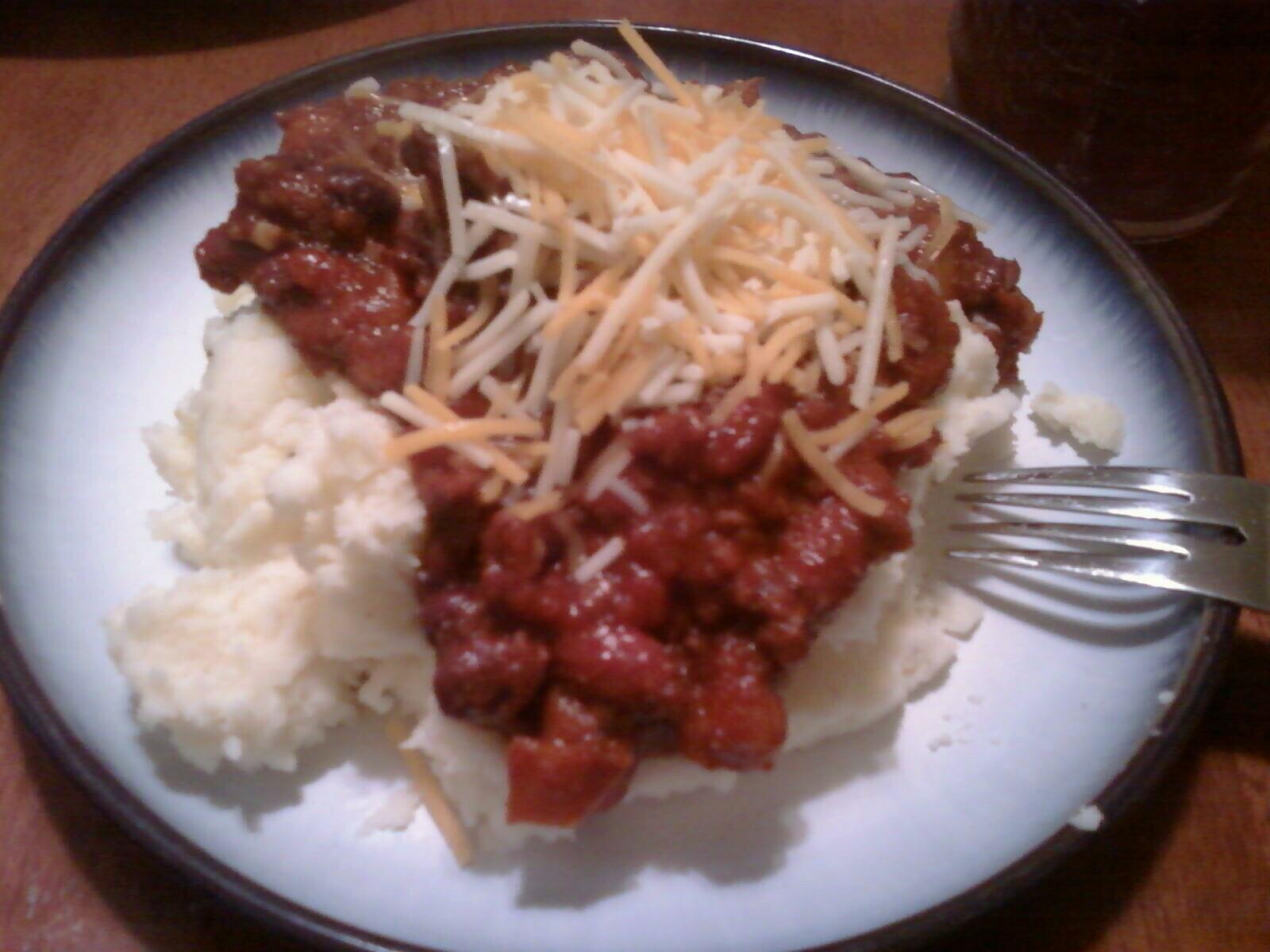 Chili à la AiXeLsyD over mashed potatoes... topped with shredded triple cheddar.